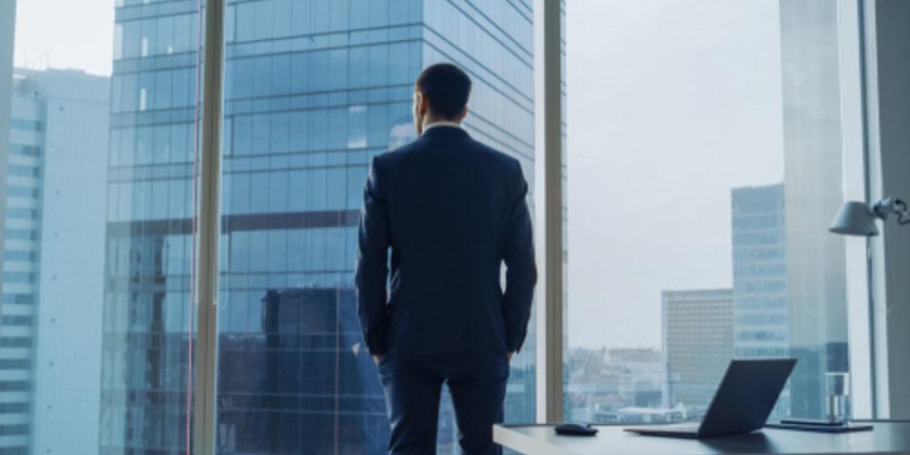 Man standing infront of corporate window